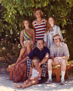 This was taken in 1974, when my parents were 40 and I was 5. We posed under the avocado tree that held my tree house, and you can see the pool reflected in the men's glasses. My siblings are Martha, David, Shannon, and Larry. I don't know why I had such a sour expression, but I bet it's because they made me sit on the ground since I was the littlest.