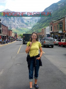 "Standing under the race banner on Telluride's main street, Colorado Avenue, the day before the race. The summit we cross during the race is hiding behind the ridge that's behind the ""I"" in ""Imogene"" on the banner."